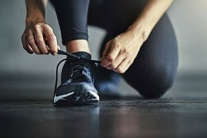 Running shoe being tied with two hands by person bending down on one knee