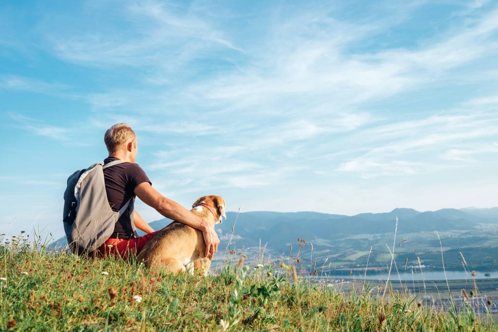 Man with his dog resting on a hike representing enjoyment after using natural pain relief products by NeoRelief