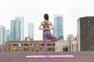 woman practicing yoga on top of building, looking out over city